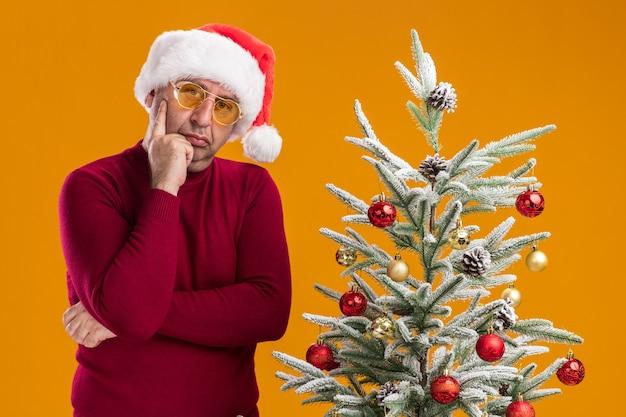 Mann mittleren alters, der weihnachtsweihnachtsmütze im dunkelroten rollkragenpullover und in der gelben brille trägt, die kamera verwirrt betrachten, die neben einem weihnachtsbaum über orange hintergrund steht
