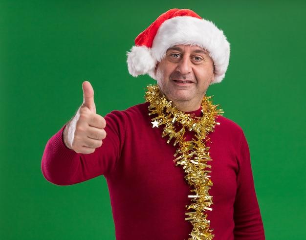 Mann mittleren alters, der weihnachtsweihnachtsmütze mit lametta um den hals mit lächeln auf gesicht trägt, das daumen oben zeigt