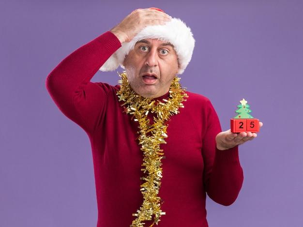 Mann mittleren alters, der weihnachtsweihnachtsmütze mit lametta um den hals trägt, der spielzeugwürfel mit datum fünfundzwanzig betrachtet kamera besorgt und verwirrt mit hand auf seinem kopf steht über lila hintergrund