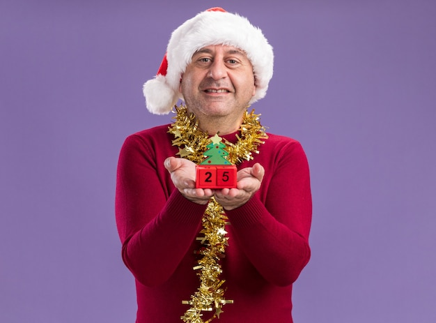Mann mittleren alters, der weihnachtsweihnachtsmütze mit lametta um den hals trägt, der spielzeugwürfel mit datum fünfundzwanzig betrachtet kamera betrachtet, die fröhlich über lila hintergrund stehend lächelt