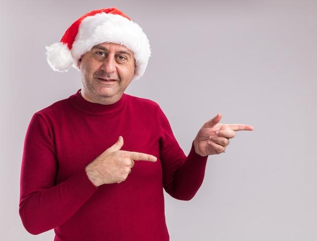Mann mittleren alters, der weihnachtsweihnachtsmütze trägt, die kamera mit lächeln auf gesicht zeigt, das mit indexfignern auf die seite zeigt, die über weißem hintergrund steht
