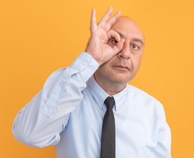 Mann mittleren alters, der weißes t-shirt mit krawatte trägt, die blickgeste zeigt, die auf orange wand lokalisiert wird