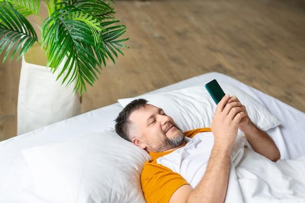 Mann mittleren alters im bett, der nach dem aufwachen seine nachrichten im smartphone überprüft
