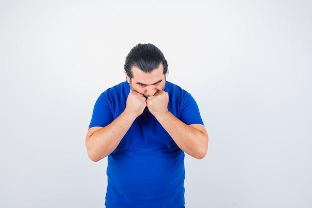 Mann mittleren alters im blauen t-shirt, das fäuste auf mund hält und ernsthafte vorderansicht sieht.