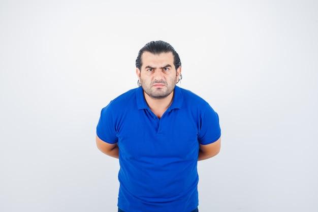 Mann mittleren alters im blauen t-shirt, das kamera betrachtet, während hände hinter dem rücken hält und ernsthafte vorderansicht schaut.