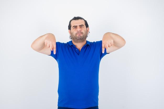 Mann mittleren alters im blauen t-shirt, das nach unten zeigt und selbstbewusst, vorderansicht schaut.