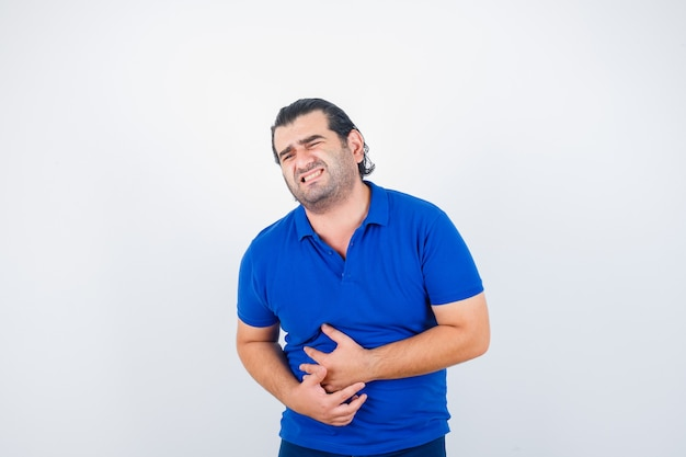 Mann mittleren alters im blauen t-shirt, das unter bauchschmerzen leidet und unwohl schaut, vorderansicht.