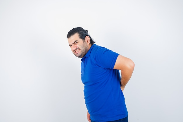 Mann mittleren alters im blauen t-shirt, das unter rückenschmerzen leidet und unwohl schaut, vorderansicht.