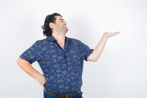Mann mittleren alters im hemd, das etwas zeigt und glücklich schaut, vorderansicht.