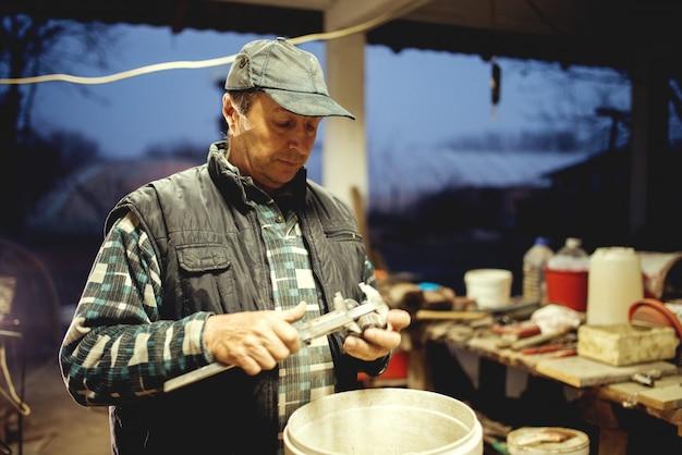 Mann mittleren alters in der werkstatt spät in der nacht hart arbeiten.
