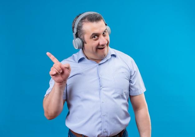 Mann mittleren alters in kopfhörern mit überraschter emotion auf gesicht, das zeigefinger auf einem blauen hintergrund zeigt