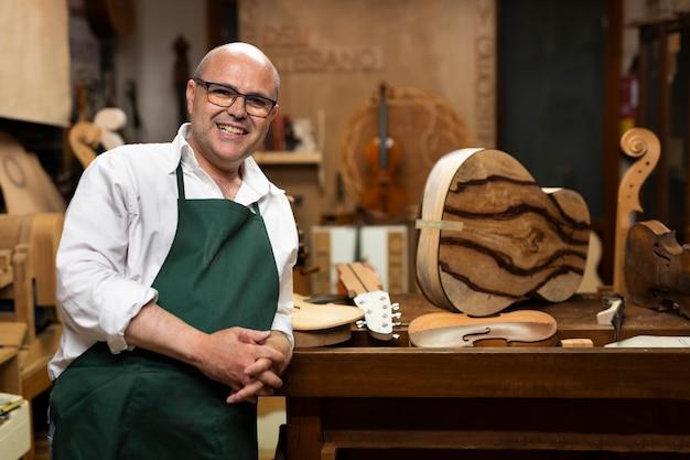Mann mittleren alters in seiner instrumentenwerkstatt