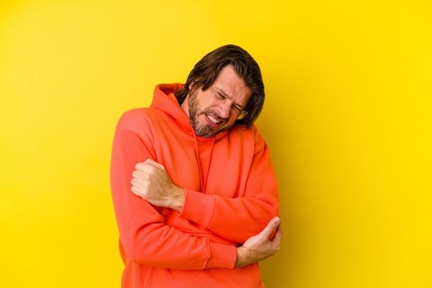 Mann mittleren alters isoliert auf gelber wand, die ellbogen massiert und nach einer schlechten bewegung leidet