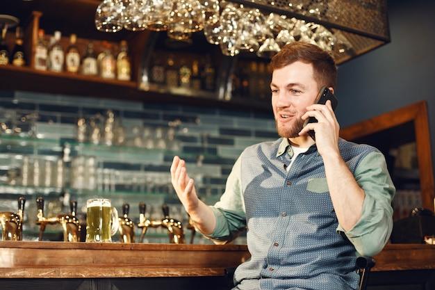 Mann mittleren alters. kerl mit einem telefon an der bar. mann in einem jeanshemd in einer zelle.