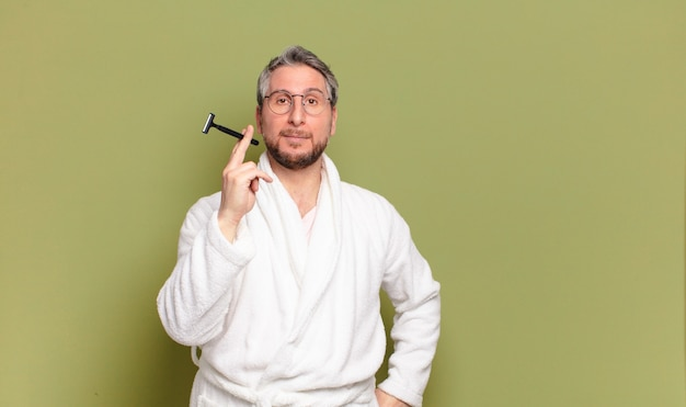 Mann mittleren alters mit bademantel und rasiermesser