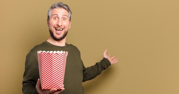 Mann mittleren alters mit einem popcorn-eimer
