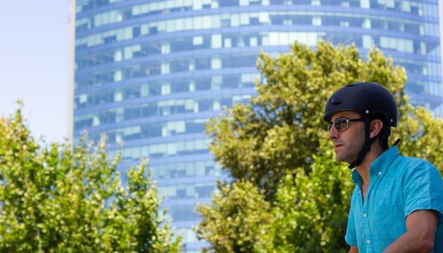 Mann mittleren alters mit helm und sonnenbrille, der an einem sonnigen tag fahrrad in der stadt fährt?