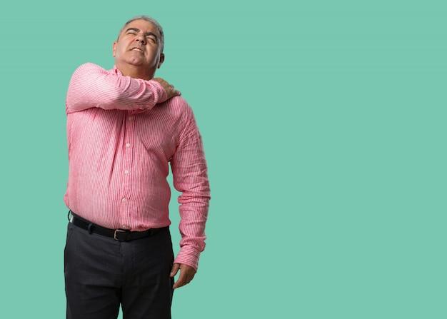 Mann mittleren alters mit rückenschmerzen aufgrund von arbeitsstress, müde und klug