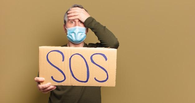 Mann mittleren alters mit schutzmaske braucht hilfe