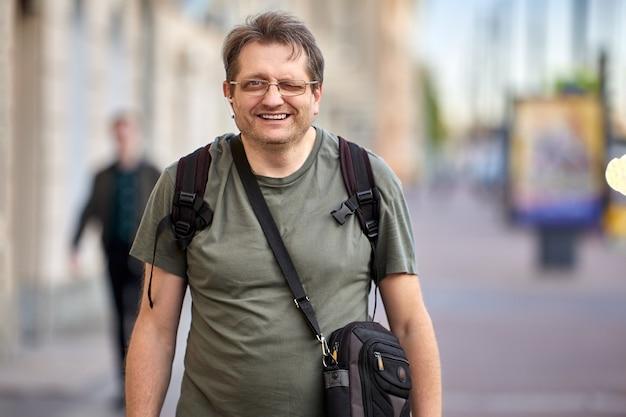 Mann mittleren alters mit umhängetasche und rucksack im freien