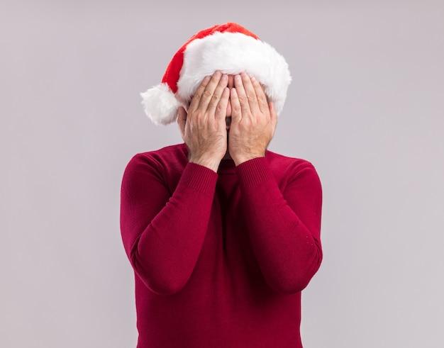 Mann mittleren alters mit weihnachtsmütze, die die augen mit den händen bedeckt, die über der weißen wand stehen?