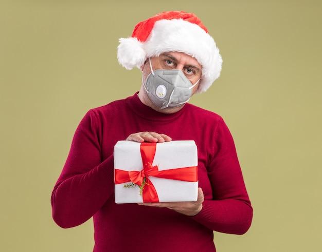 Mann mittleren alters mit weihnachtsmütze mit gesichtsschutzmaske, die weihnachtsgeschenk mit ernstem gesicht über grüner wand hält