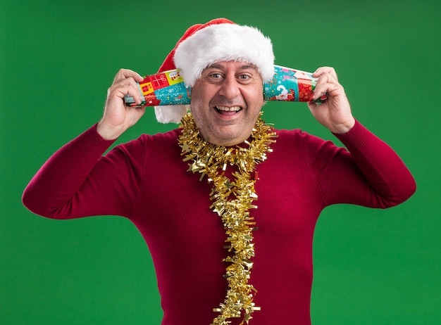 Mann mittleren alters mit weihnachtsmütze mit lametta um den hals, der bunte pappbecher über seinem ohr hält, glücklich und aufgeregt über grüner wand stehend