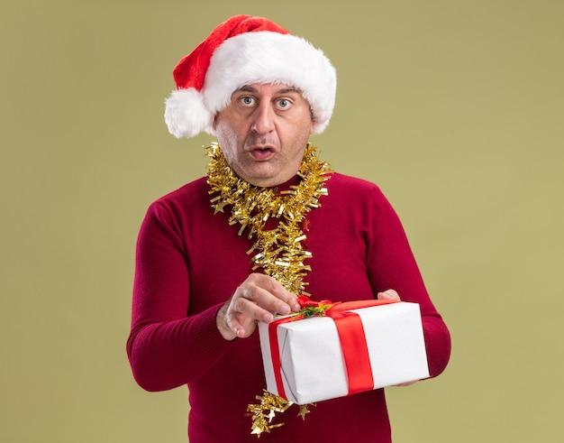 Mann mittleren alters mit weihnachtsmütze mit lametta um den hals hält weihnachtsgeschenk überrascht über grüner wand stehend