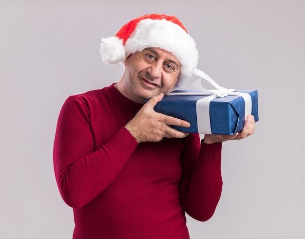Mann mittleren alters mit weihnachtsmütze mit weihnachtsgeschenk mit einem lächeln auf dem gesicht, das über weißer wand steht?