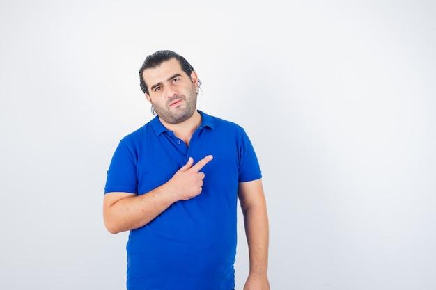 Mann mittleren alters zeigt auf die obere rechte ecke im blauen t-shirt und sieht selbstbewusst aus. vorderansicht.