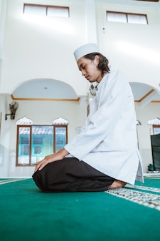 Mann muslim, der gebet in der moschee tut