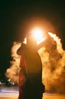 Mann nachts in der stadt mit rauch