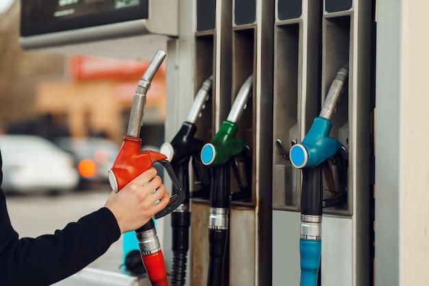 Mann nimmt die waffe auf tankstelle, detailansicht, kraftstofffüllkonzept. benzintanken, benzin- oder dieseltankservice