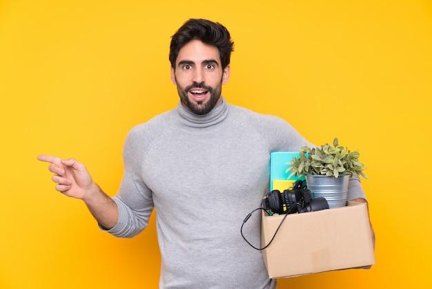 Mann nimmt eine kiste voller dinge und macht einen schritt