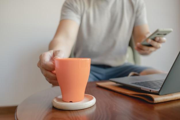 Mann nimmt eine orange kaffeetasse auf, während er an seinem laptop arbeitet.