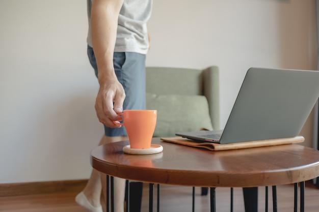 Mann nimmt kaffeetasse auf, während er an seinem laptop arbeitet.