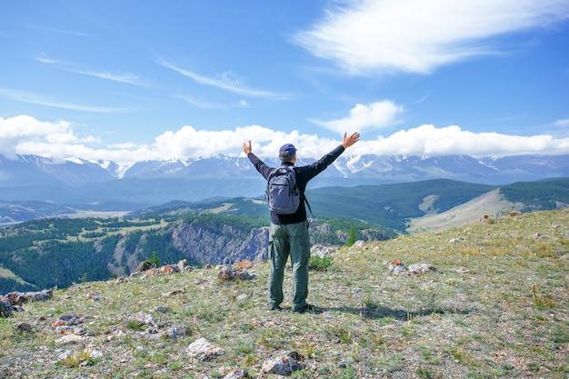 Mann oben auf berg. männlicher tourist auf berg. aktives lebensstil-reiseabenteuer der ferien im freien