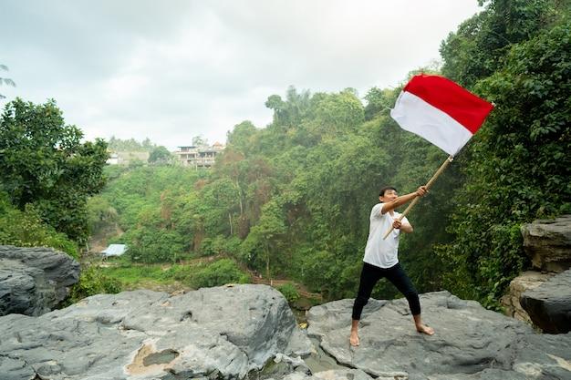 Mann oben auf dem hügel am morgen aufsteigende indonesische flagge, die unabhängigkeitstag feiert