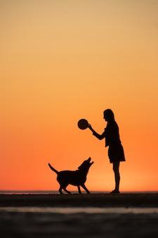 Mann oder frau spazieren mit dem hund bei sonnenuntergang einen spaziergang am see oder meer bei sonnenuntergang