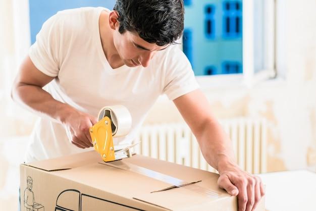 Mann oder heimwerker, der verpackungskasten auf band aufnimmt