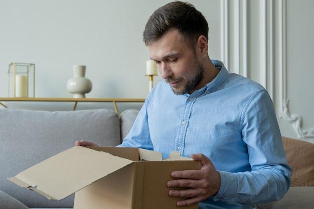Mann öffnet eine paketbox zu hause, während er auf der couch sitzt