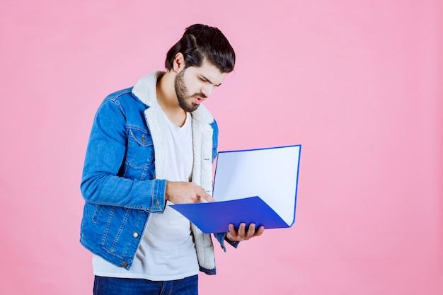 Mann öffnet einen blauen ordner und überprüft ihn