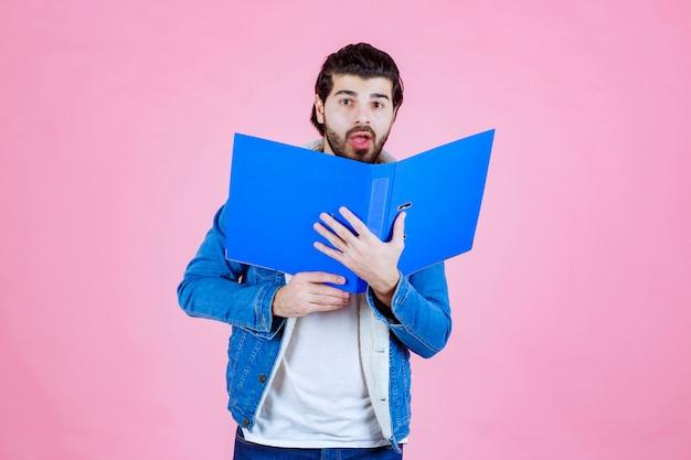 Mann öffnet einen blauen ordner und versteckt sein gesicht dahinter
