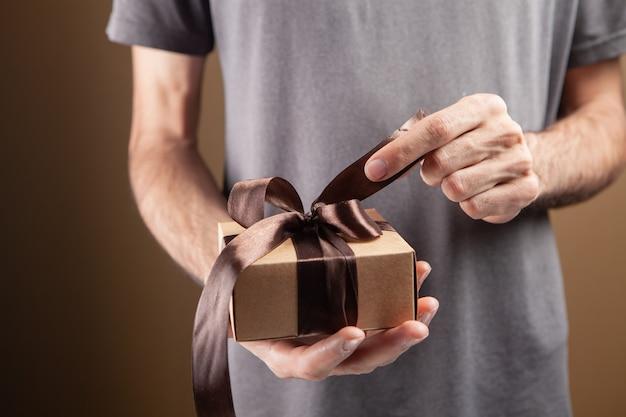 Mann öffnet geschenkband auf braunem hintergrund