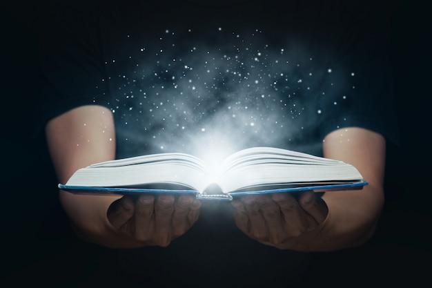 Mann öffnete ein magisches buch mit wachsenden lichtern und magischem pulver. lern- und bildungskonzept