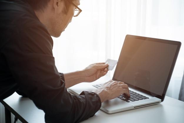 Mann online über laptop einkaufen und mit kreditkarte bezahlen