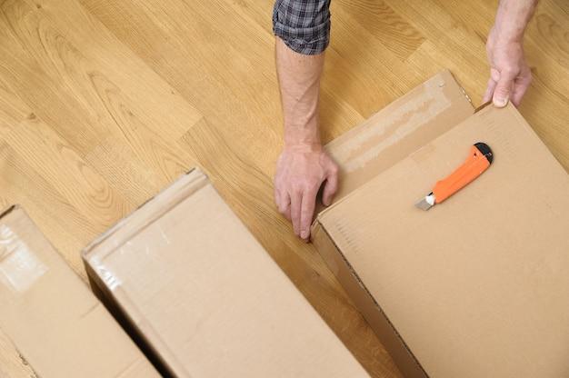 Mann packt die pappkartons aus es öffnet die seite der verpackung