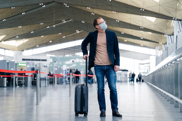 Mann passagier mit koffer im internationalen flughafen trägt schützende gesichtsmaske