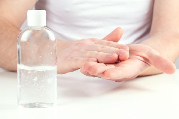Mann person, die kleine tragbare antibakterielle händedesinfektionsmittel auf händen verwendet.