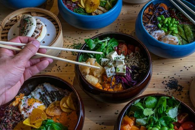 Mann pflücke essen von hand mit stäbchen in die poke bowl auf einem holztisch.